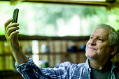 elderly man thumbing mobile phone
