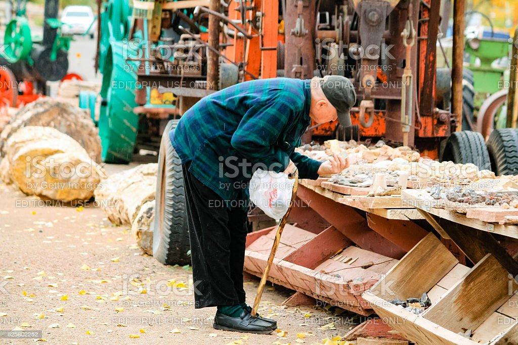 Elderly man tries to buy some stones stock photo