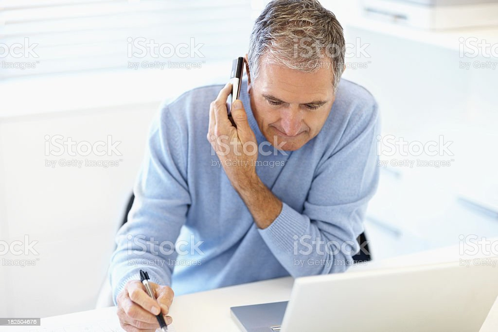 Elderly man using laptop while talking on phone royalty-free stock photo