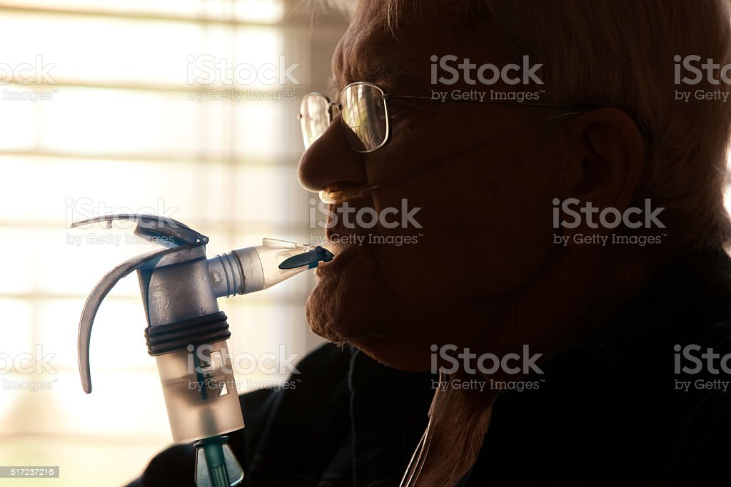 Elderly Man Using Nebulizer stock photo