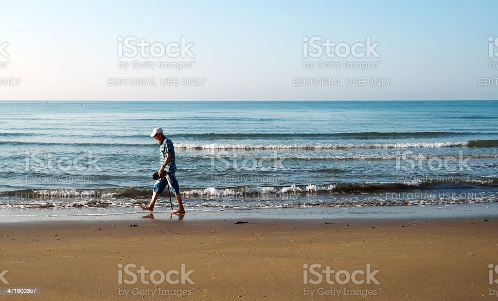 Elderly man walking on the beach. Color Image royalty-free stock photo