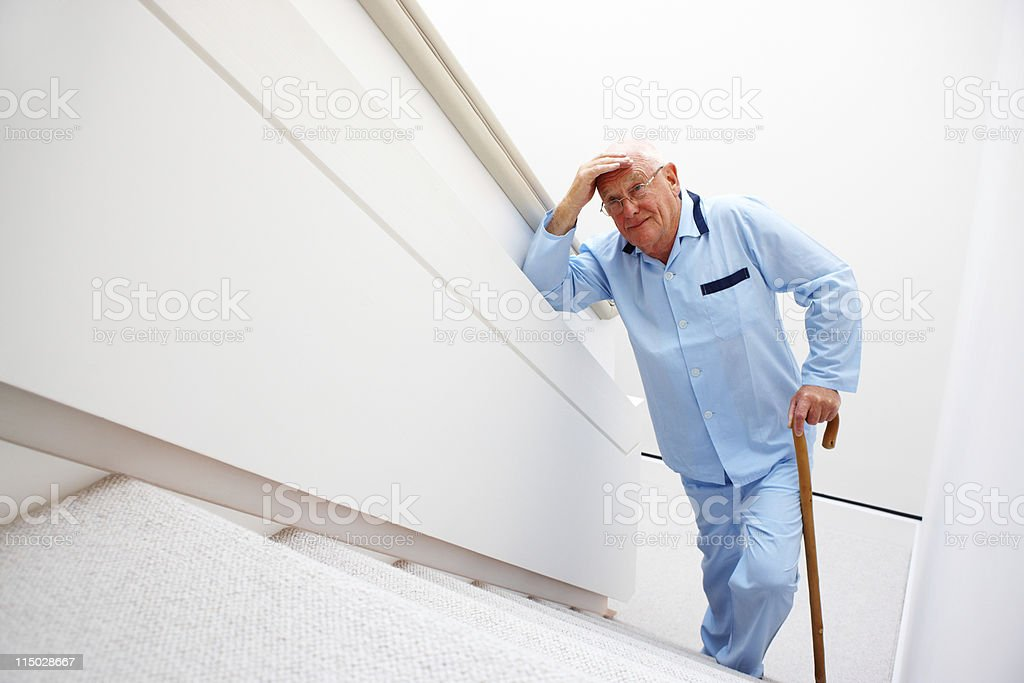 Elderly Man Walking Up a Set of Stairs stock photo