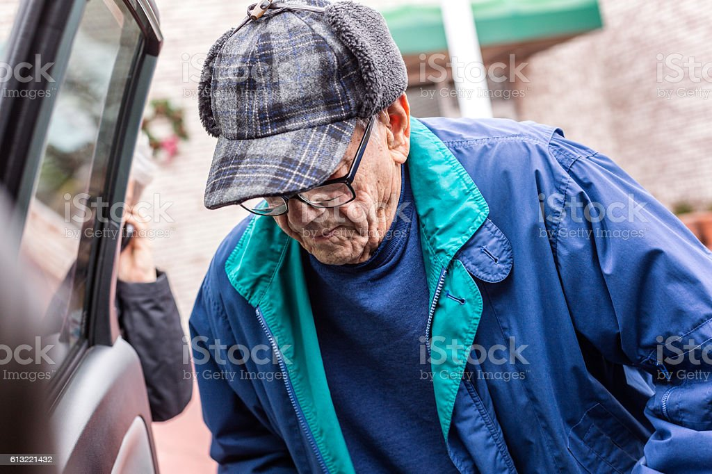 Elderly Man Warmly Dressed For Winter Getting Into Car stock photo