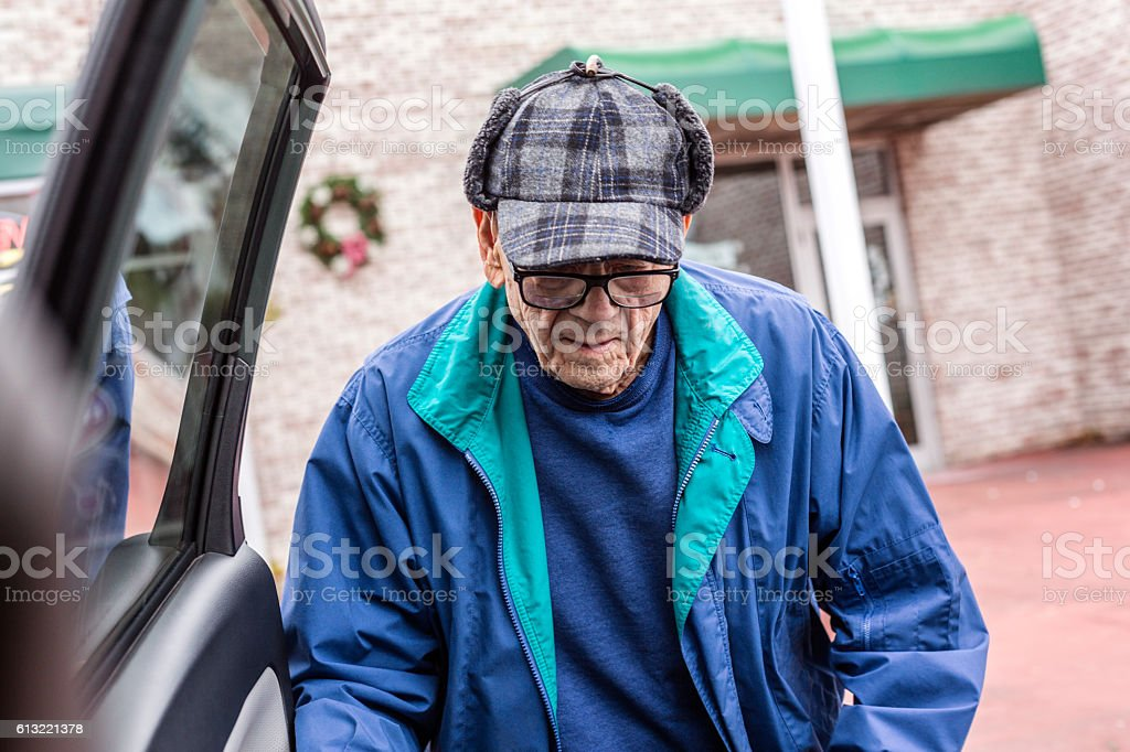 Elderly Man Warmly Dressed For Winter Shopping Trip Approaching Car stock photo