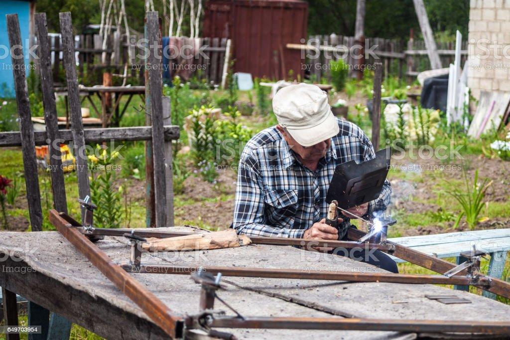 Elderly man welding metal construction stock photo