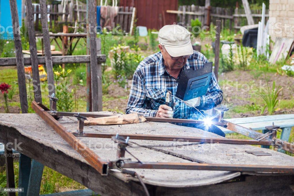 Elderly man welding metal structure stock photo