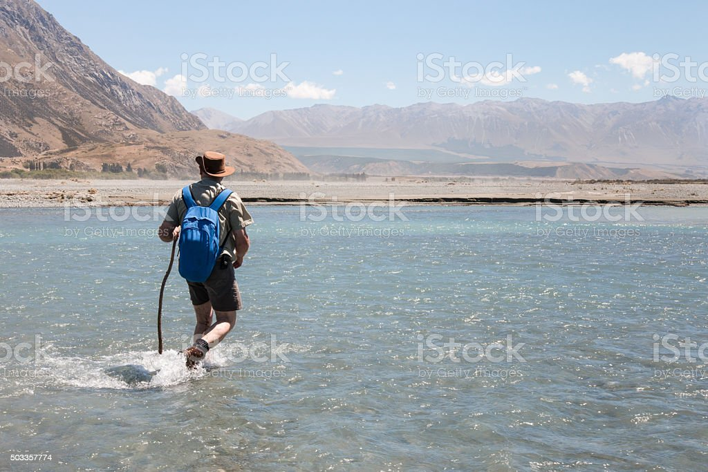 Elderly man with a backpack crossing a river ford stock photo