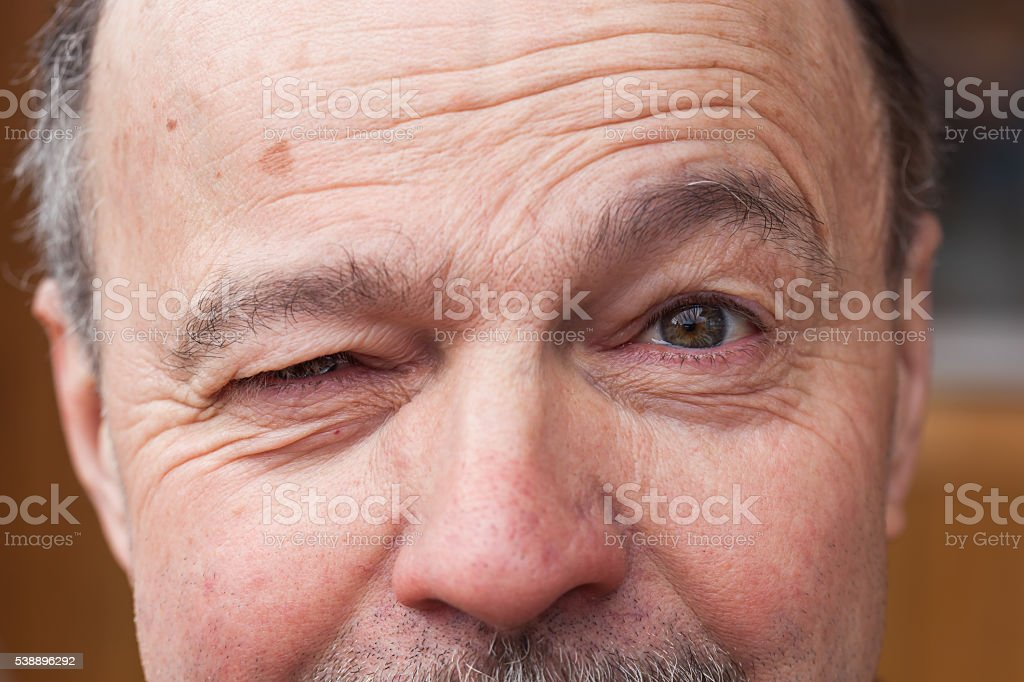 elderly man with a mustache and wrinkles winks stock photo