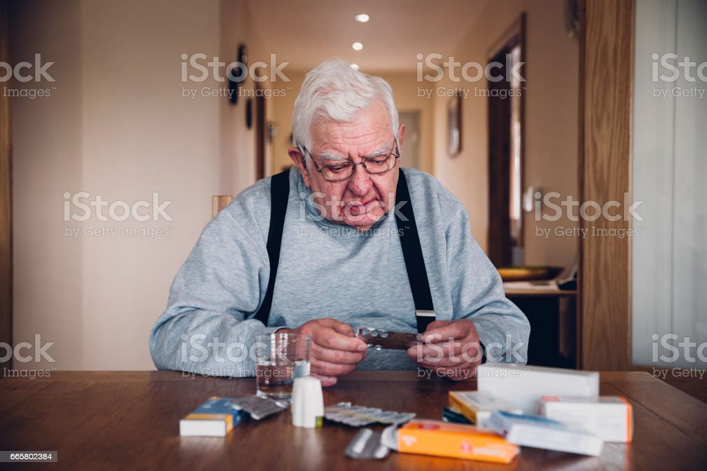 Elderly Man with all his Medication stock photo