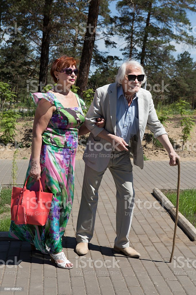 Elderly man with back pain walks with his wife stock photo