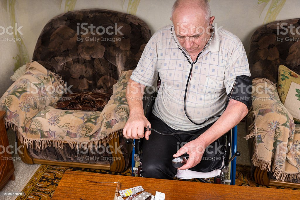 Elderly Man with Special Needs Checking his BP stock photo