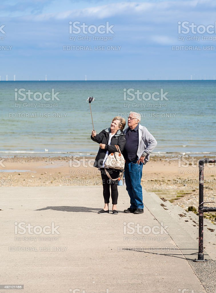 Elderly man woman tourists taking selfies using a digital camera. stock photo