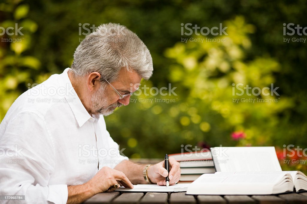 Elderly man writing and reading outside royalty-free stock photo