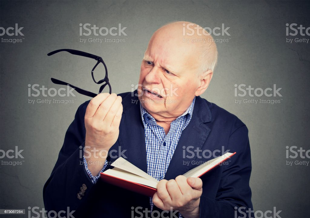 elderly, mature man holding book, glasses having eyesight problems unable to read stock photo