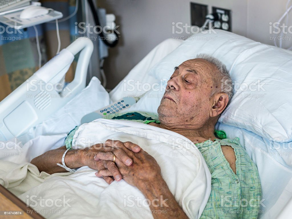 Elderly Medical Patient Man Resting in Hospital Bed stock photo