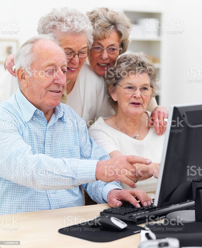 Elderly men and women using computer at home royalty-free stock photo