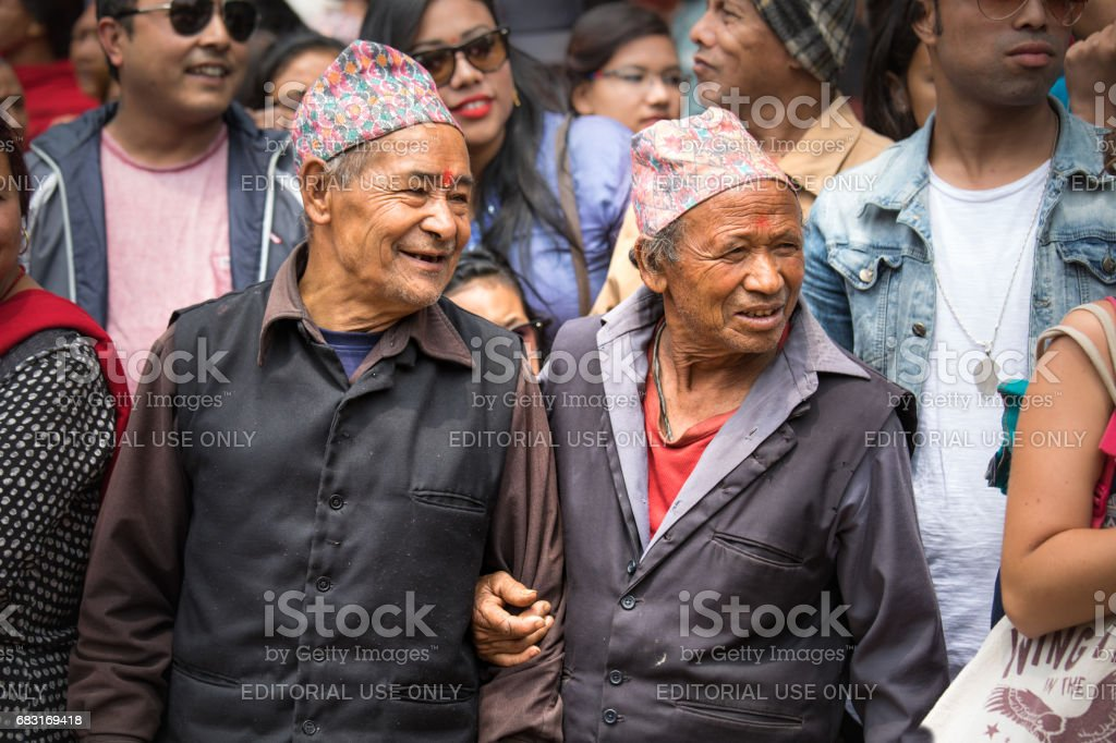 Elderly men watching a ceremonial procession. stock photo