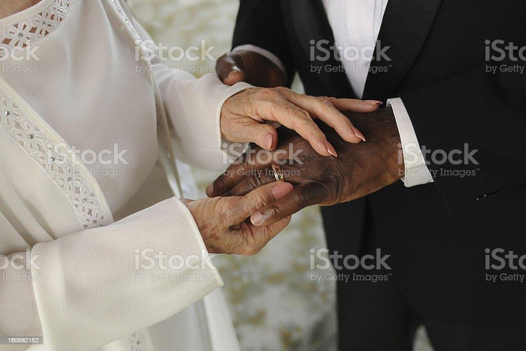 elderly mixed couple exchanging wedding rings royalty-free stock photo