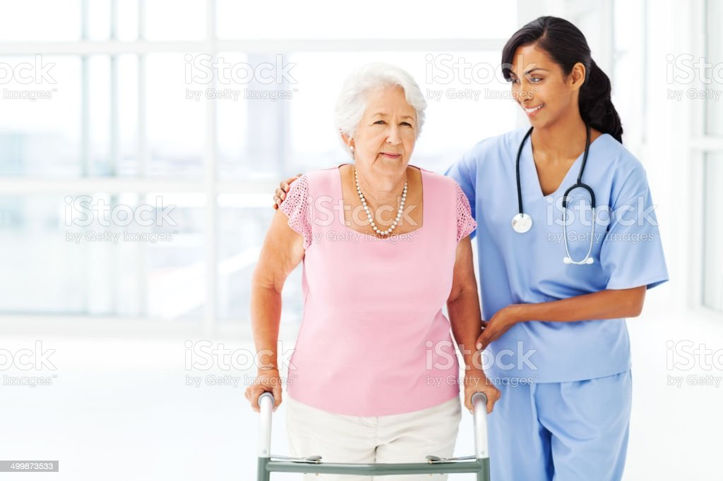 Elderly Patient Being Assisted By Nurse In Using Walker stock photo