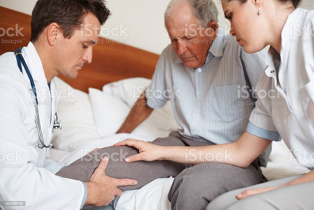 Elderly patient being assisted by two doctors stock photo