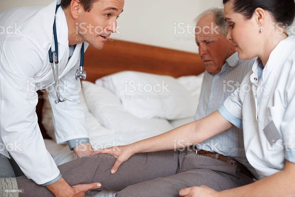 Elderly patient being examined by two doctors royalty-free stock photo