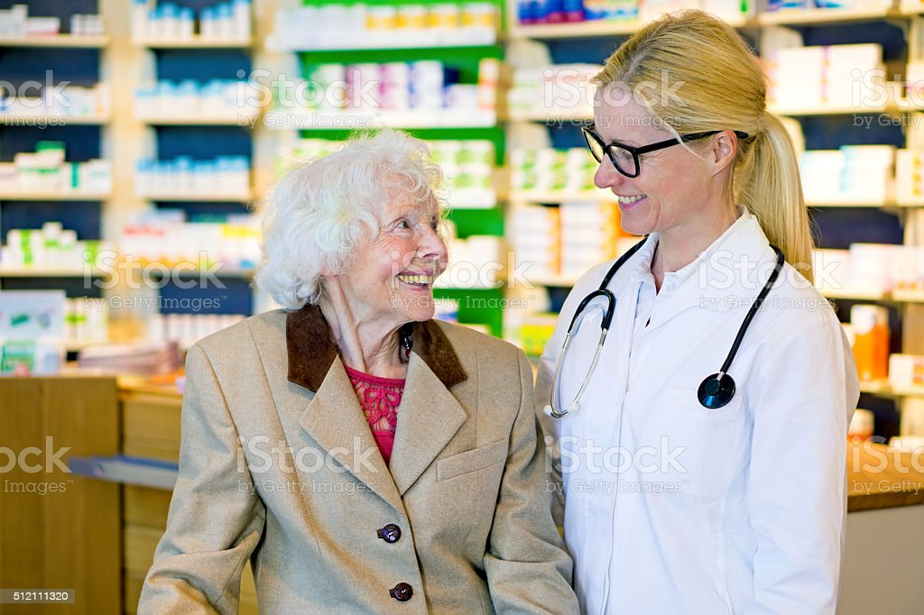 Elderly patient happy with her smiling doctor. stock photo