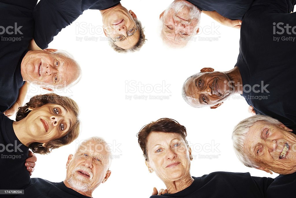 Elderly people in a huddle smiling over white royalty-free stock photo