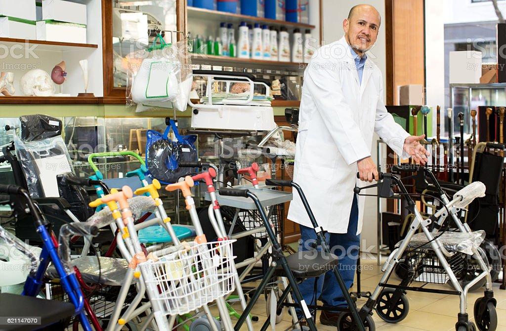 Elderly professional consultant offering orthopaedic goods stock photo