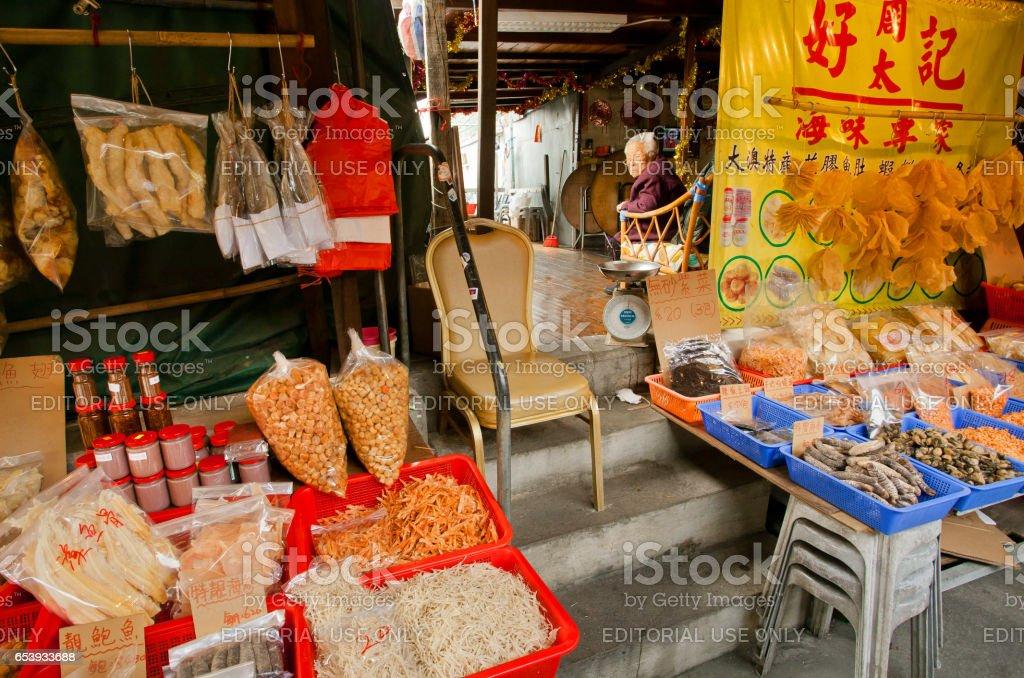 Elderly seller of dry seafood om market street of fishing village stock photo