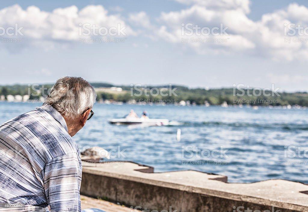 Elderly Senior Adult Man Admiring Lake Water Speed Boat stock photo