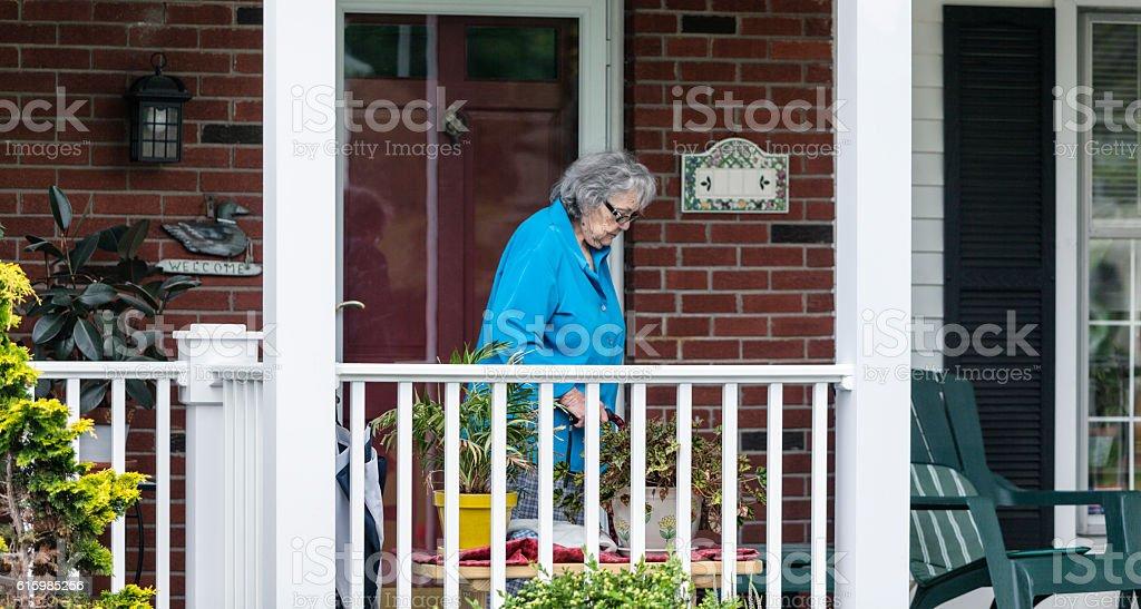 Elderly Senior Adult Woman Tending Home Front Porch Flowers stock photo