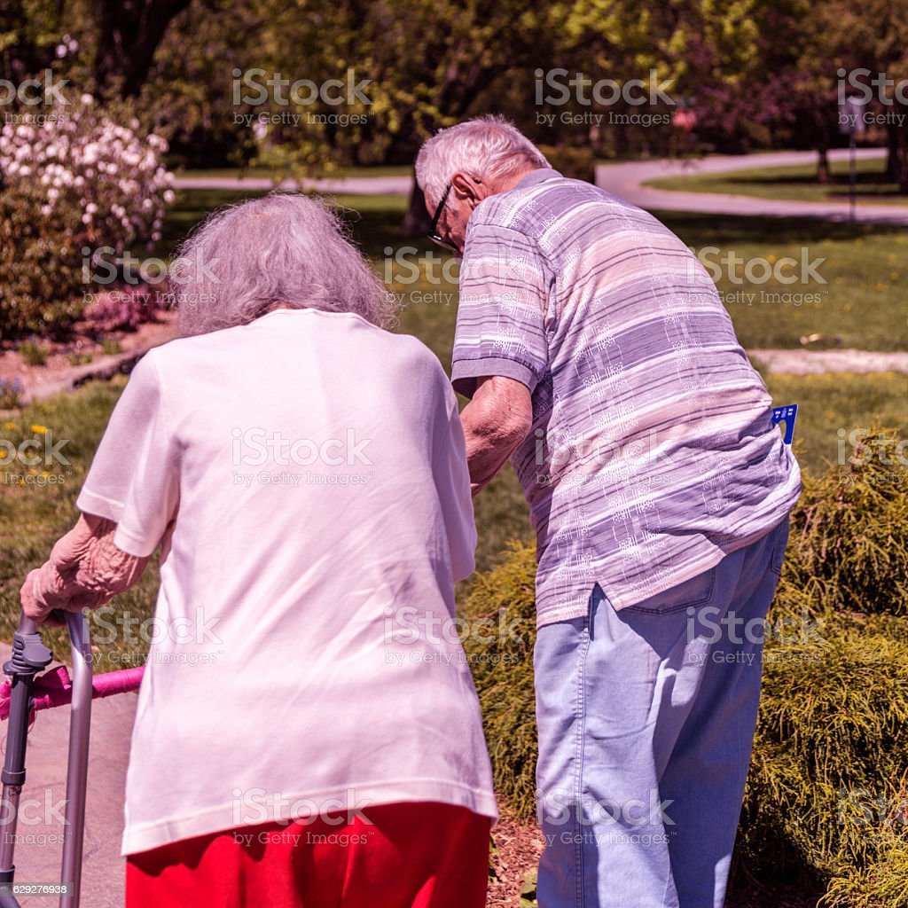 Elderly Senior Couple Walking Side By Side After Arriving Home stock photo