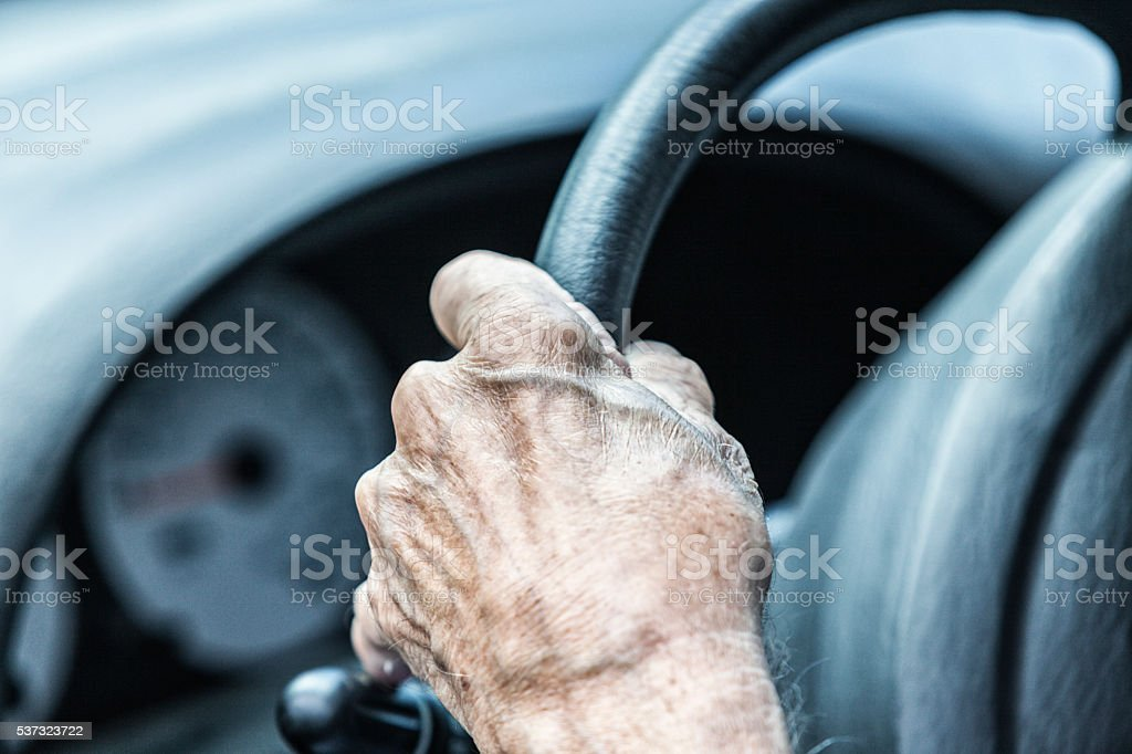 Elderly Senior Man Driver Hand Gripping Car Steering Wheel Close-Up stock photo