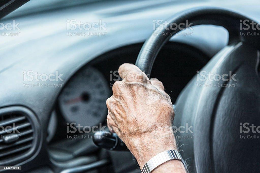 Elderly Senior Man Driver Hand Gripping Car Steering Wheel stock photo
