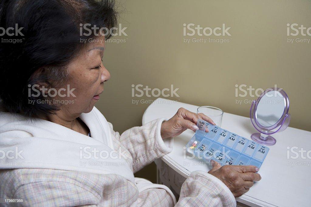 Elderly senior smiling at the mirror while taking medication royalty-free stock photo