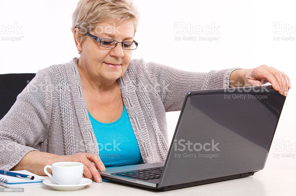 Elderly senior woman closing laptop on table at home stock photo