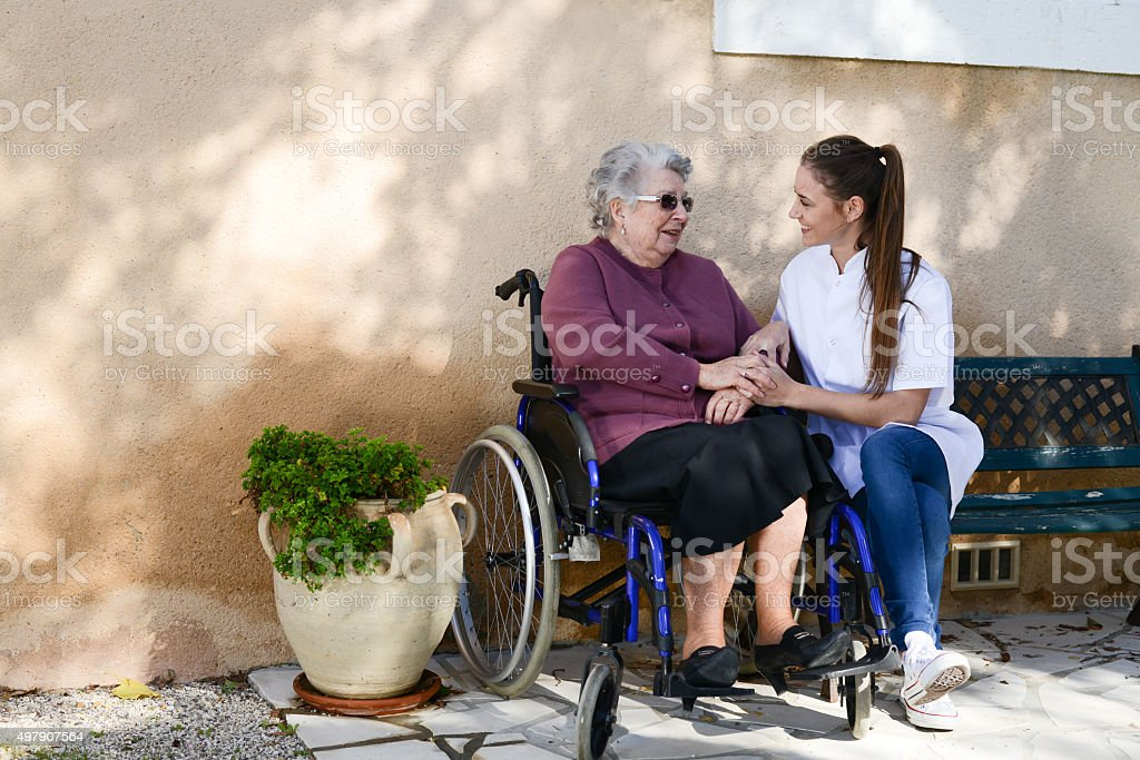 elderly senior woman on wheelchair with nurse outdoor nursing home stock photo