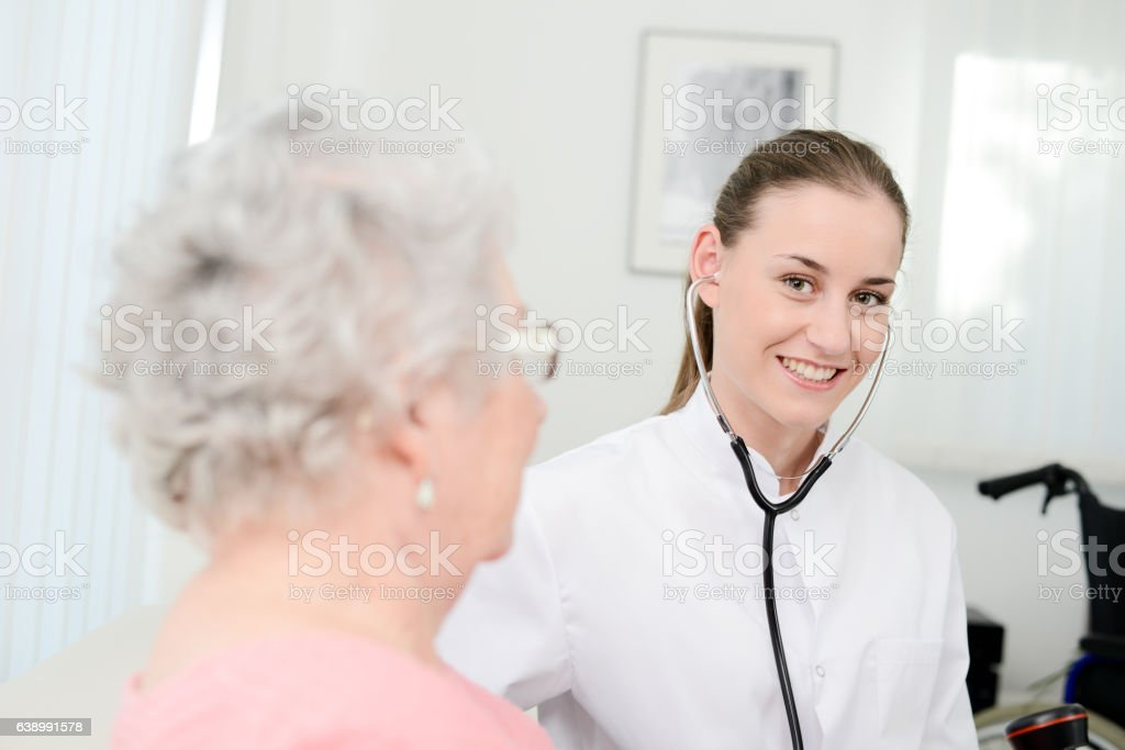 elderly senior woman with young doctor having medical care home stock photo
