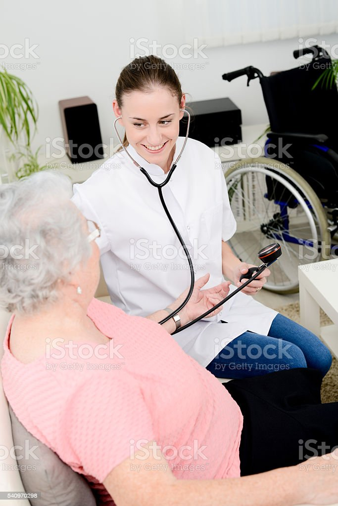 elderly senior woman with young doctor medical care at home stock photo