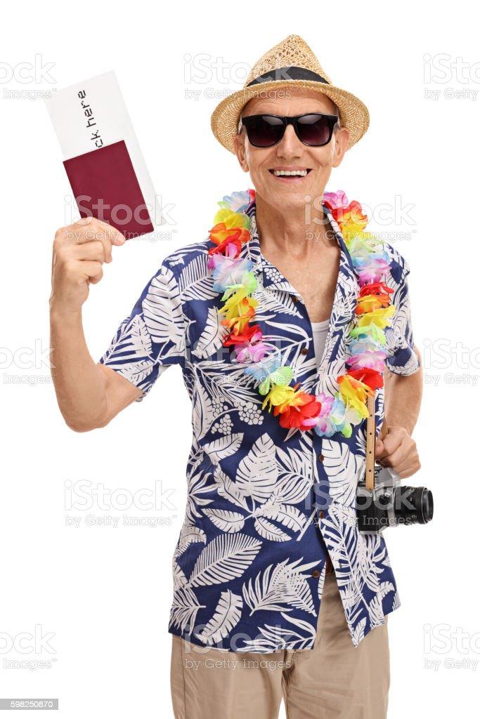 Elderly tourist holding a passport and a camera stock photo