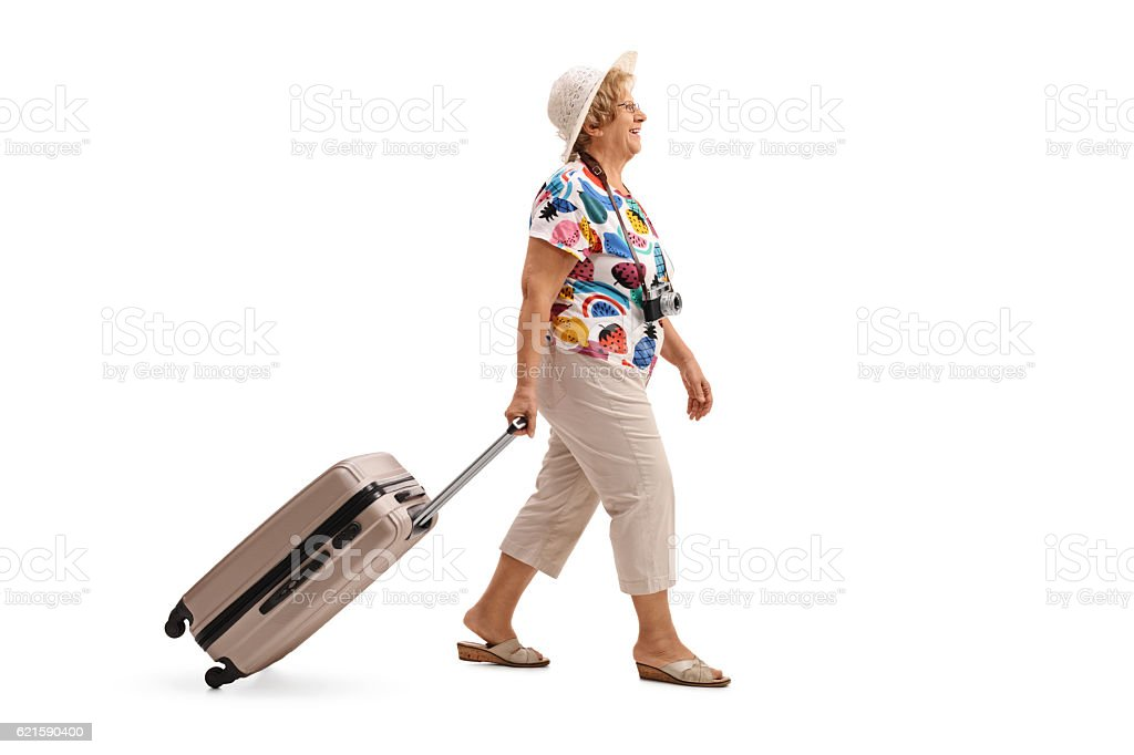 Elderly tourist walking and pulling a suitcase stock photo