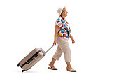 Elderly tourist walking and pulling a suitcase