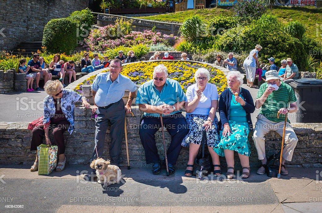 Elderly tourists enjoying sunshine ice cream on seaside holidays England stock photo