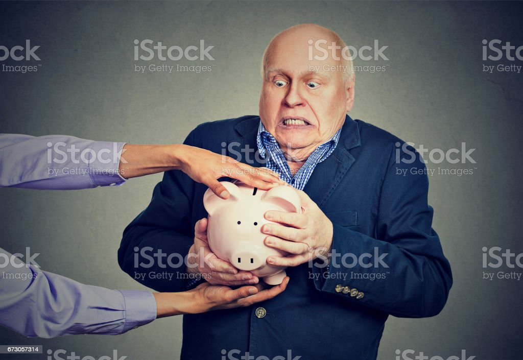 Elderly upset scared business man holding piggy bank trying to protect his savings from being stolen stock photo