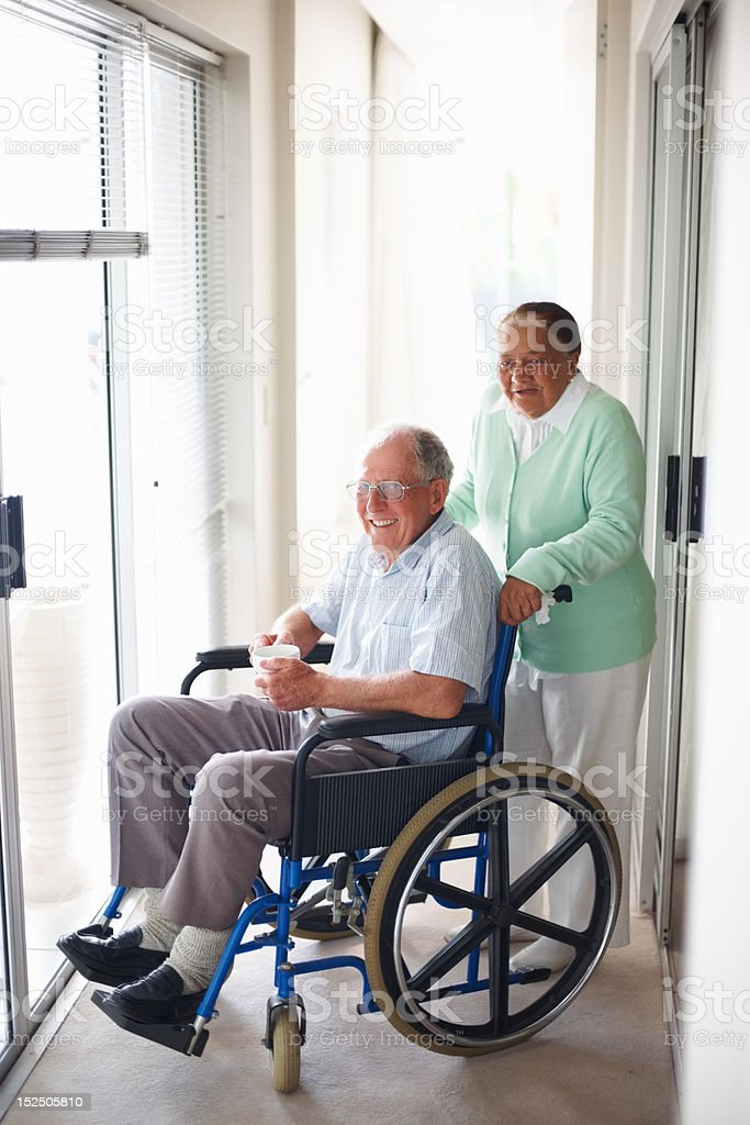 Elderly wife assisting her husband sitting on wheelchair royalty-free stock photo