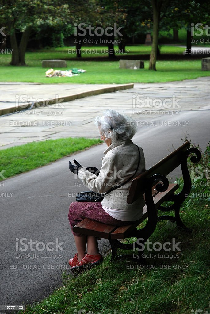 Elderly woman adjusting her gloves sit on bench in Liverpool stock photo