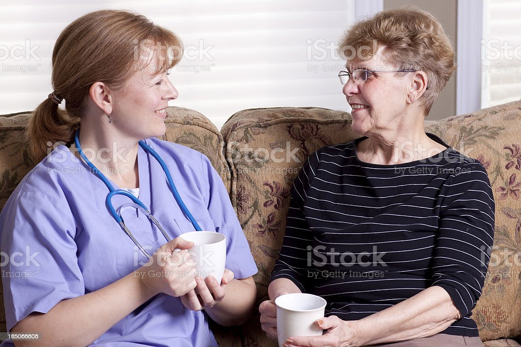 Elderly woman and caregiver on sofa with coffee royalty-free stock photo