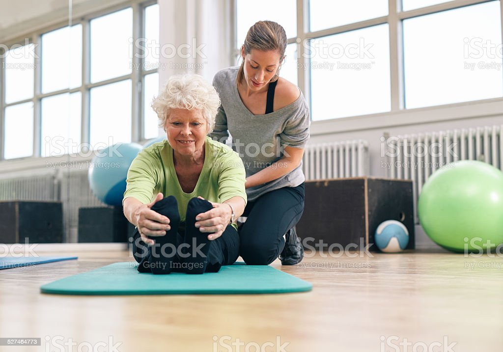 Elderly woman being helped by her instructor in the gym stock photo