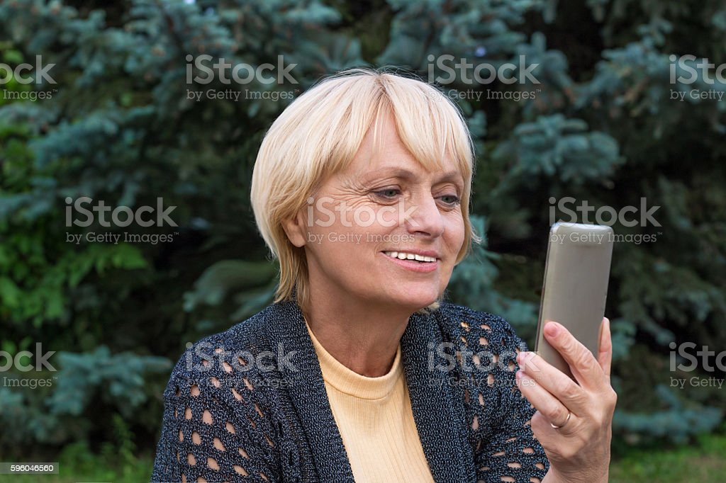 Elderly woman chats by video messenger on mobile phone stock photo