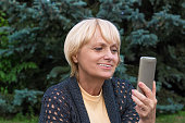 Elderly woman chats by video messenger on mobile phone